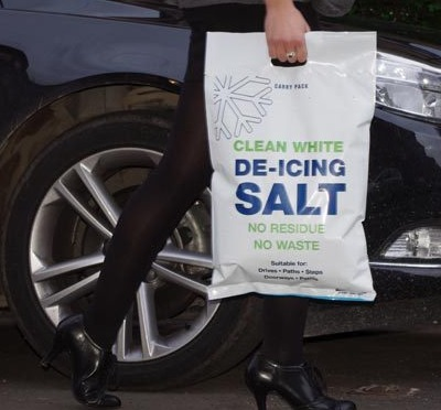 Lady in high heels carrying easy to handle white salt 10kg carry bag